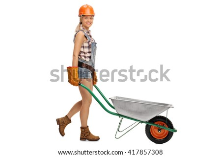 Cheerful construction woman pushing an empty wheelbarrow isolated on white background - stock photo
