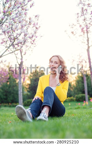 Cheerful conversation. Attractive young woman talking by phone while sitting on grass in spring park. - stock photo