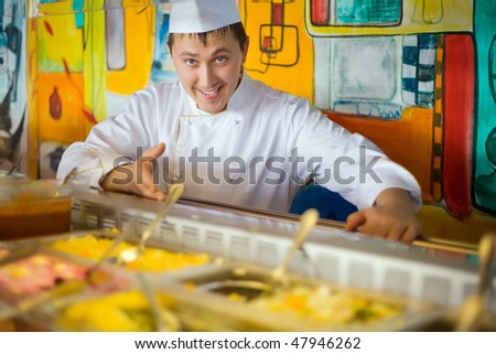 cheerful cook in uniform near counter with meal - stock photo