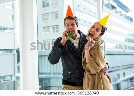 Cheerful couple celebrating birthday against glass window at office - stock photo