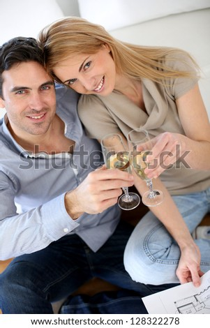 Cheerful couple celebrating with glass of sparkling wine - stock photo