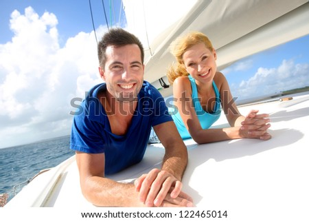 Cheerful couple cruising on a sail boat - stock photo