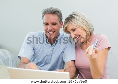 Cheerful couple doing online shopping with debit card and laptop in the living room at home - stock photo