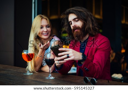 Cheerful couple drinking aperitif in a cocktail bar and having a pleasant conversation - Friends taking selfie with phone