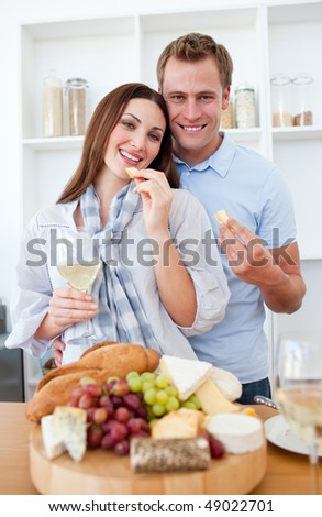 Cheerful couple drinking white wine and eating cheese in the kitchen - stock photo