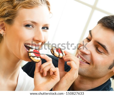 Cheerful couple eating cookies