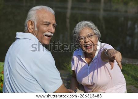 Cheerful couple enjoying at park , woman pointing at something