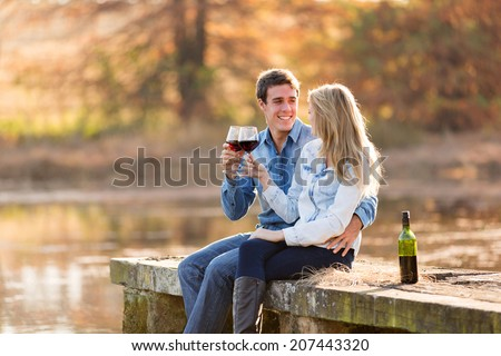 cheerful couple enjoying glass of red wine by the pond - stock photo