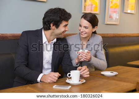 Cheerful couple flirting at coffee bar table - stock photo