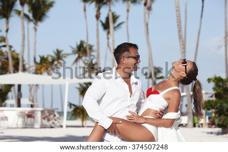 Cheerful couple having fun, dancing on a white sandy beach. Caribbean paradise. - stock photo