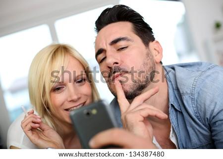 Cheerful couple having fun using smartphone - stock photo