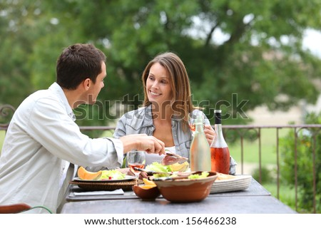 Cheerful couple having lunch in hotel garden