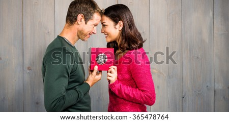 Cheerful couple holding gift box against pale grey wooden planks - stock photo