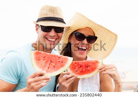 cheerful couple holding slices of watermelon - stock photo
