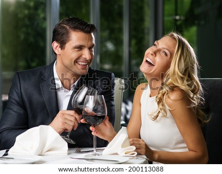 Cheerful couple in a restaurant with glasses of red wine - stock photo