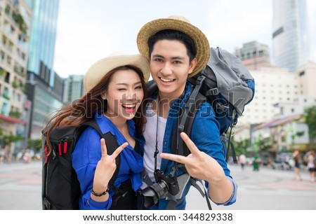 Cheerful couple in city showing thumbs up. Happy loving couple.  - stock photo