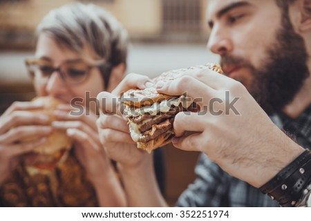 Cheerful Couple In Fast Food Reastaurant Eating Burgers