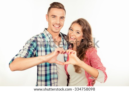 Cheerful couple in love embracing each other gesturing a heart - stock photo
