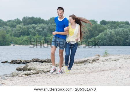 Cheerful couple in love walking on the beach - stock photo