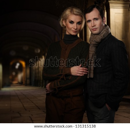Cheerful couple in smart casual wear outdoors at night - stock photo
