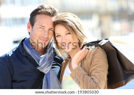 Cheerful couple in town doing shopping - stock photo