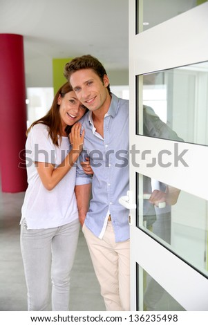 Cheerful couple inviting people to enter in home - stock photo
