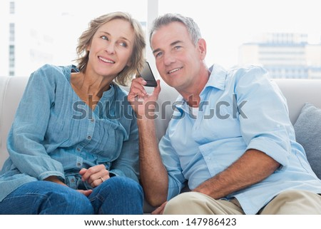 Cheerful couple listening to mobile phone together at home in the living room