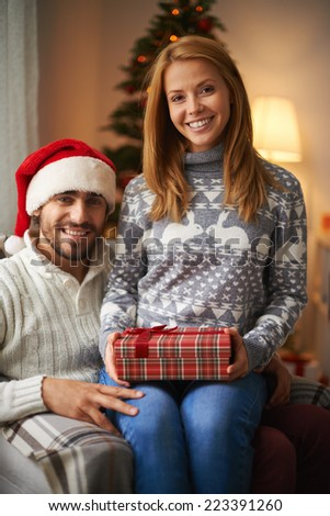 Cheerful couple looking at camera on Christmas night - stock photo