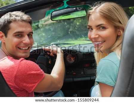 Cheerful couple looking at camera over shoulder while having a ride in cabriolet - stock photo