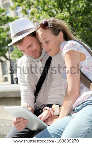 Cheerful couple looking at electronic tablet in the street