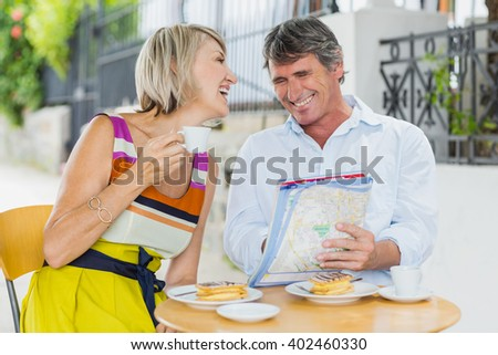 Cheerful couple looking at map while enjoying coffee in cafe - stock photo