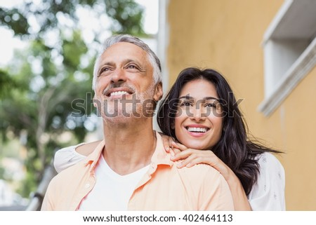 Cheerful couple looking away in city