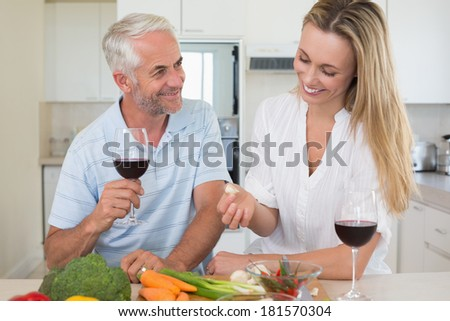 Cheerful couple making dinner together and drinking red wine at home in the kitchen - stock photo