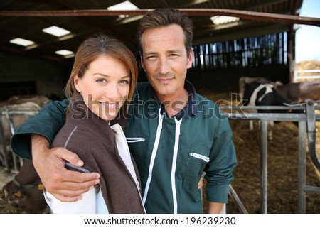 Cheerful couple of breeders standing in barn - stock photo