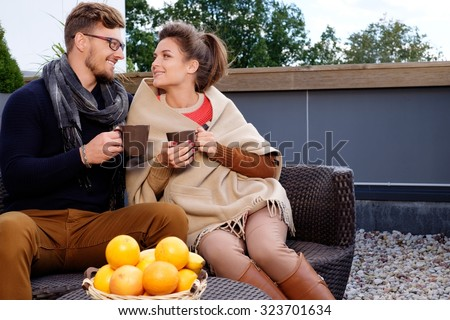 Cheerful couple on a terrace on autumn day  - stock photo