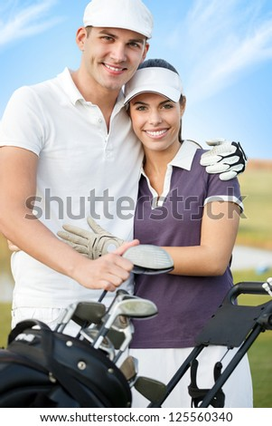 cheerful couple on golf course, hugging and looking at camera - stock photo
