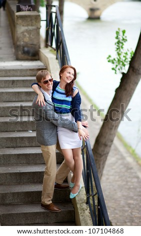 Cheerful couple on the stairs at the Seine embankment in Paris - stock photo