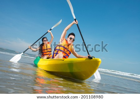 Cheerful couple paddling in kayak - stock photo