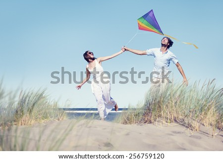 Cheerful Couple Playing Kite by the Beach - stock photo