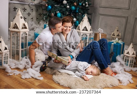 Cheerful couple reading book to toddler son beside Christmas tree, boy falling asleep - stock photo