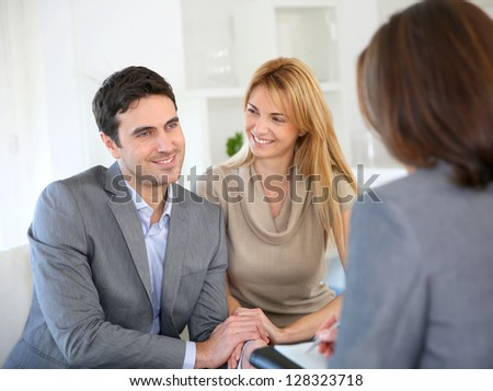 Cheerful couple receiving good news from advisor - stock photo