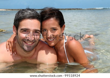 Cheerful couple relaxing in lagoon water - stock photo