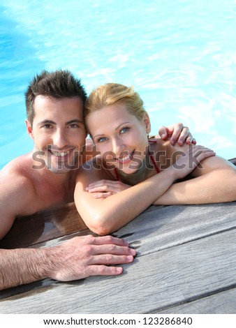 Cheerful couple relaxing in swimming pool - stock photo