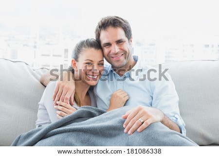 Cheerful couple relaxing on their sofa smiling at camera under blanket at home in the living room - stock photo