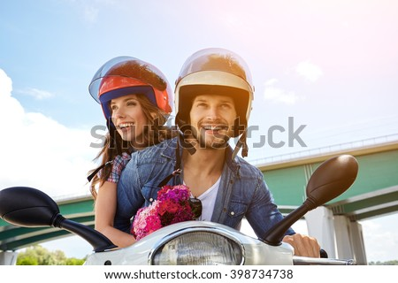Cheerful couple riding vintage scooter