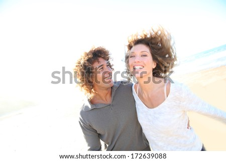 Cheerful couple running on the beach