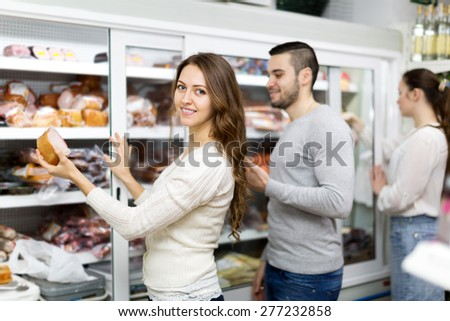 Cheerful couple selecting ham in vacuum packing at store - stock photo