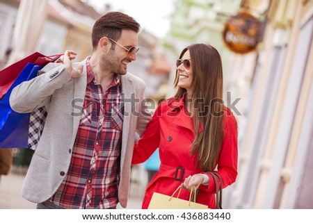 Cheerful couple shopping together in the city - stock photo