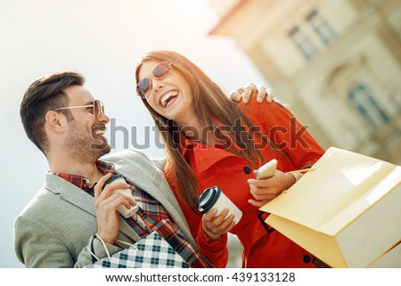 Cheerful couple shopping together in the city.They are enjoying in shopping together. - stock photo