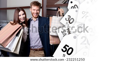 Cheerful couple show their purchases after shopping on sell-out - stock photo
